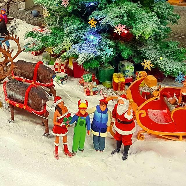 Fragment świątecznej wystawy w Kolejkowie. Renifery, sanie, elfki, Mikołaj, choinka.