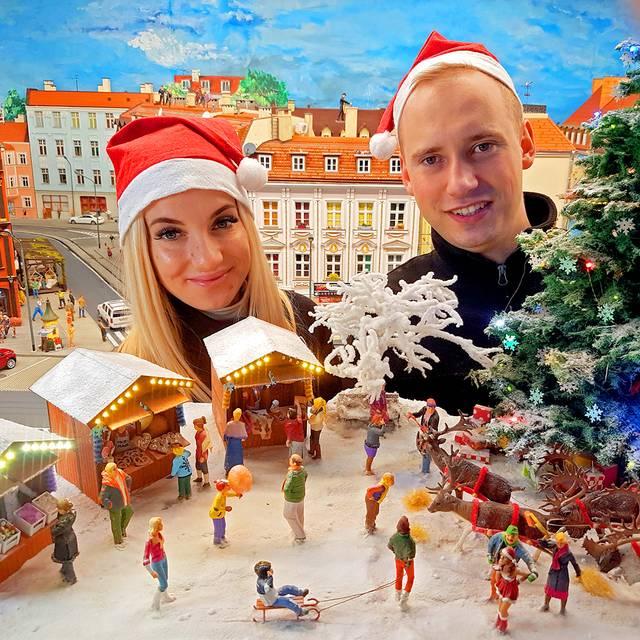 Kobieta i mężczyzna w czapkach mikołajowych na tle świątecznej makiety w Kolejkowie